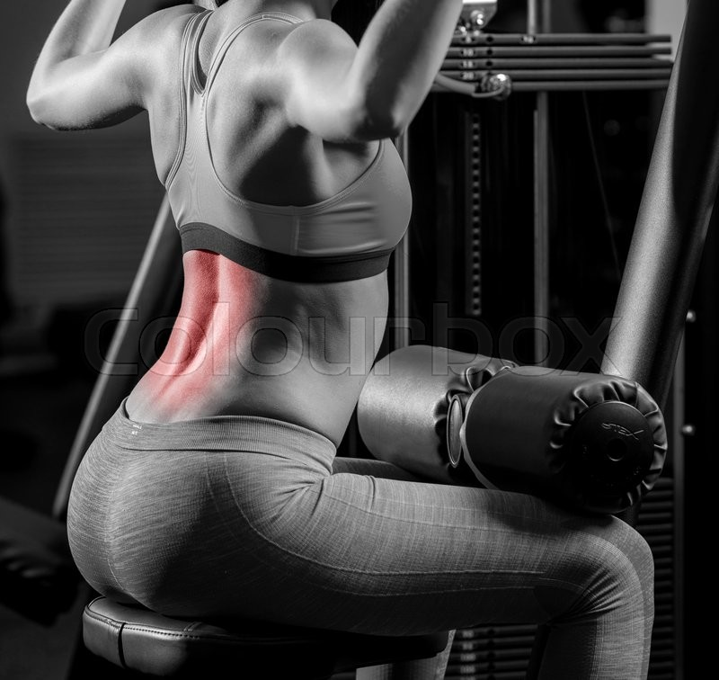 Stock image of 'Woman exercising in sports club and having backache'