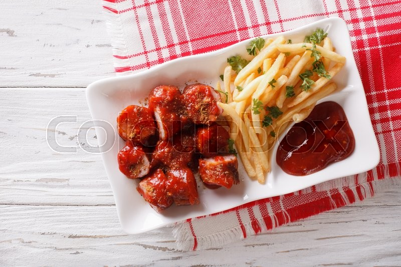 Stock image of 'German cuisine: currywurst with french fries on a plate. horizontal top view '