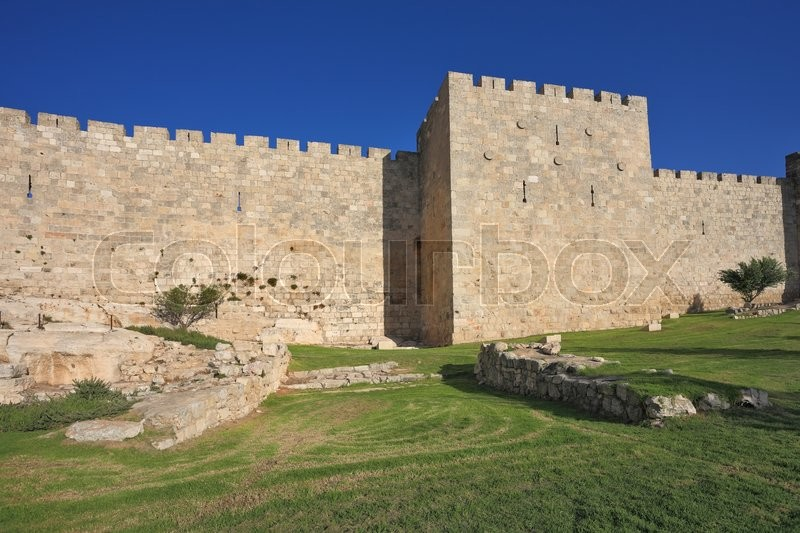 Stock image of 'Wonderful green lawn.  Defensive wall of the ancient holy Jerusalem, lit by the bright sun'