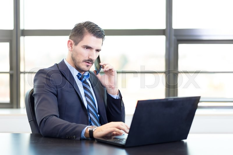 Stock image of 'Portrait of successful corporate businessman in bright modern office focused on data on his laptop computer while talking on mobile phone. Business and entrepreneurship concept.'
