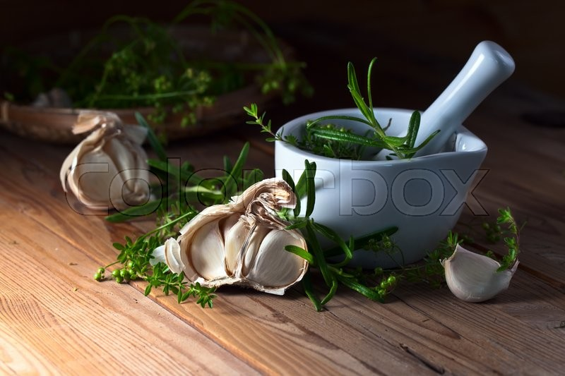 Stock image of 'garlic and  ceramic mortar with green spices'