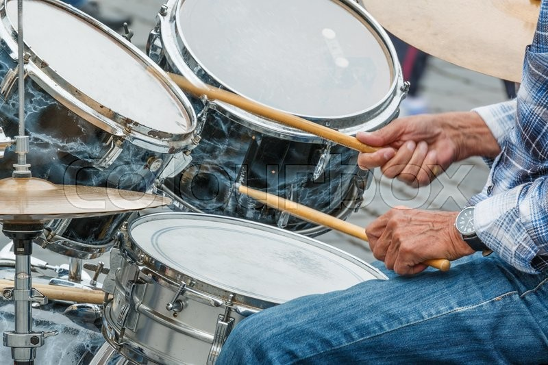 Stock image of 'Photo shows close-up of of city drummer and his hands during a day.'