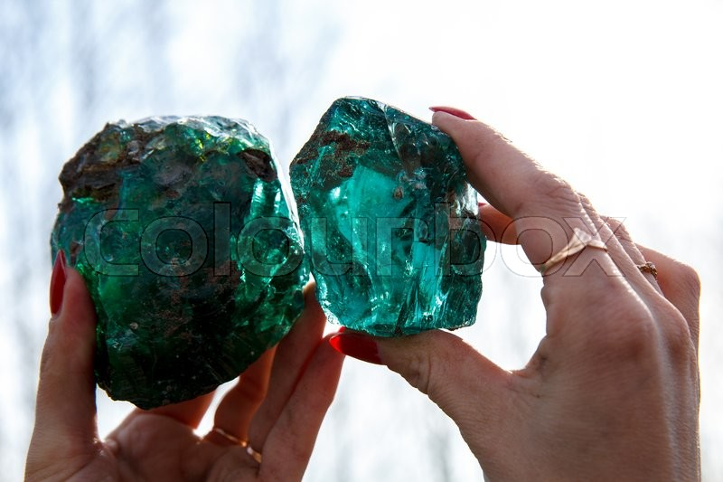 Stock image of 'A woman holding two raw glass rocks'