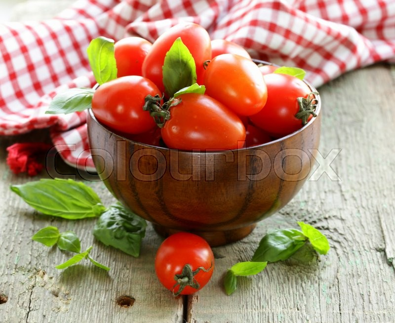 Stock image of 'cherry tomatoes with basil leaves in a wooden bowl'