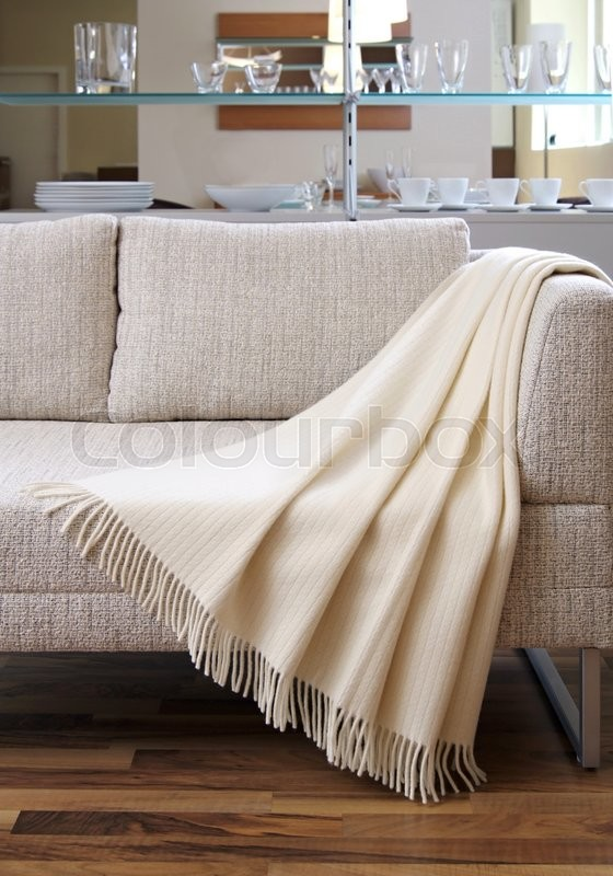 Stock image of 'Cream throw draped over a settee\'