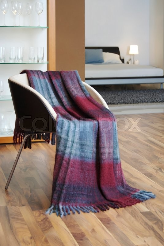 Stock image of 'Plaid draped over a chair'
