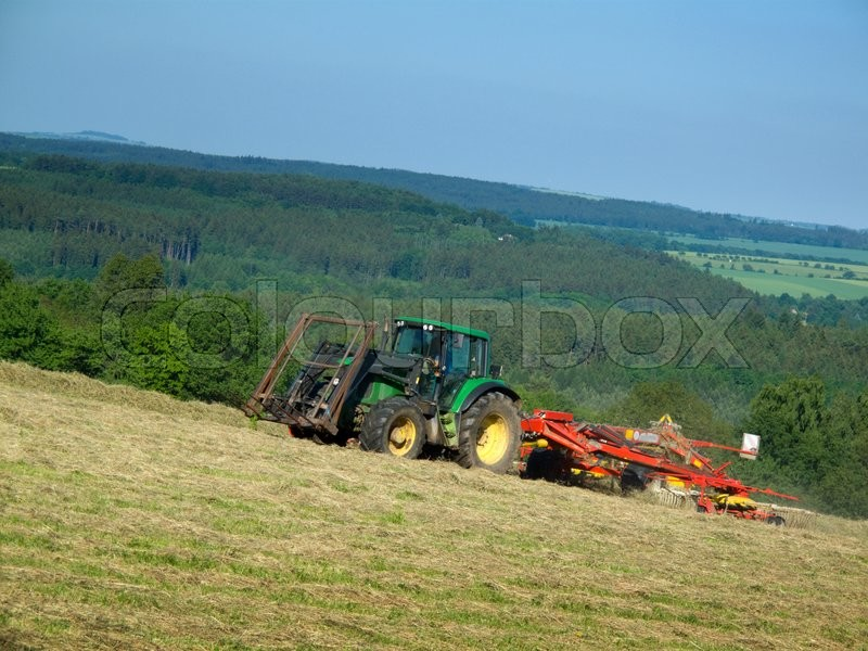 Stock image of 'Tractor with a rotary rake forming hay windrows '