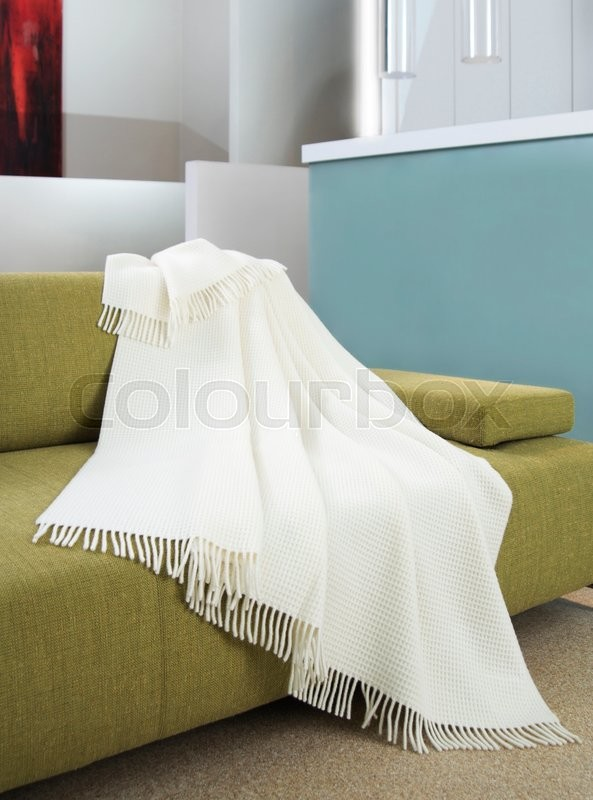Stock image of 'White throw draped over a green settee'