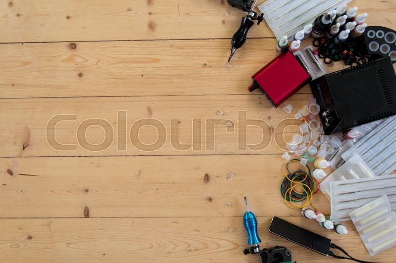 Stock image of 'Tattoo machines and equipment on the wooden background'