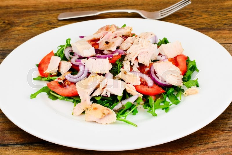 Stock image of 'Salad with Arugula, Tomatoes, Turkey Breast, Grape Seed Oil, Soy Sauce Studio Photo'