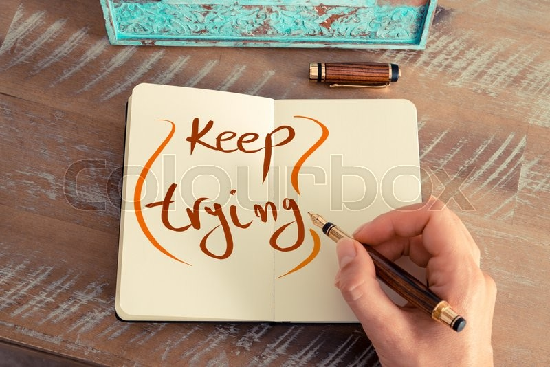 Stock image of 'Retro effect and toned image of a woman hand writing a note with a fountain pen on a notebook. Handwritten text KEEP TRYING, business success concept'