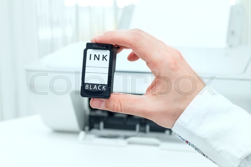 Stock image of 'Man shows black ink cartridge from white printer'