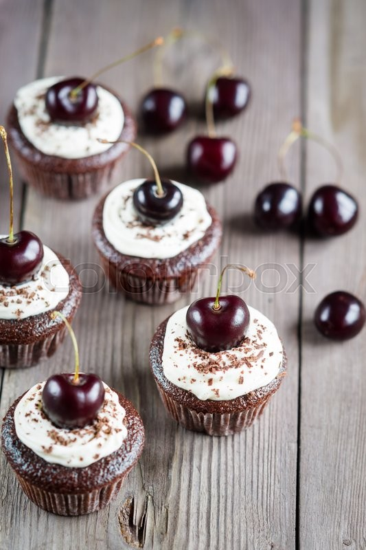 Stock image of 'Chocolate Cupcakes with cherries on wooden background'