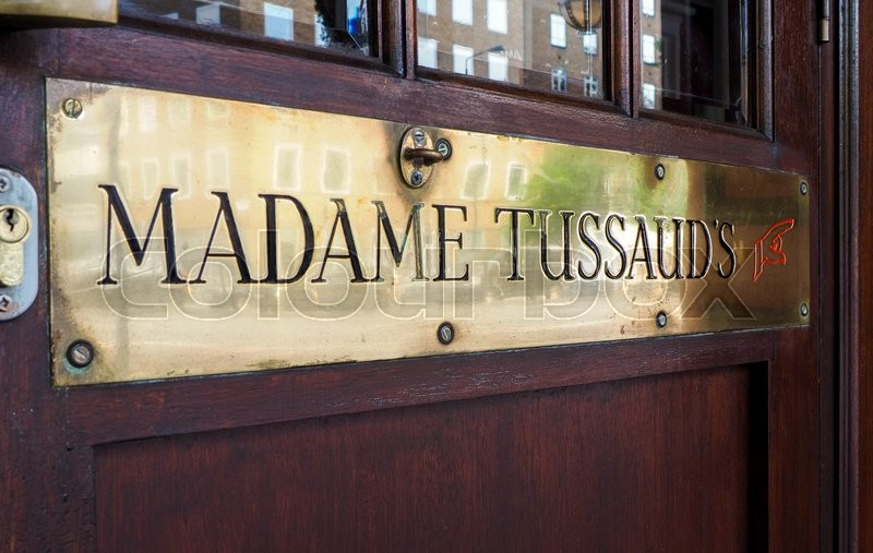 Editorial image of 'London, Uk - JUNE 12TH, 2015 - Detail of entrance of Madame Tussaud's museum with brass ensign and wooden door.'