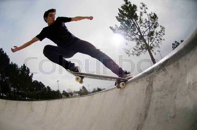 Stock image of 'Skateboarder doing a tail slide on a croncrete pool at the skate park.'