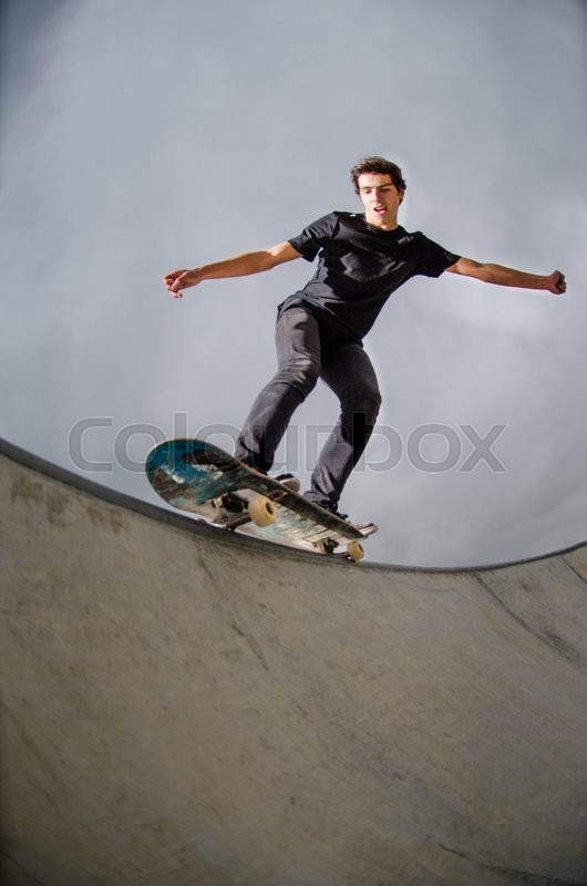 Stock image of 'Skateboarder doing a grind on a croncrete pool at the skate park.'
