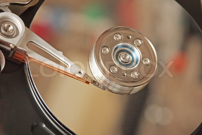 Inside hard drive. Head and surface of disk with colourful reflections, stock photo