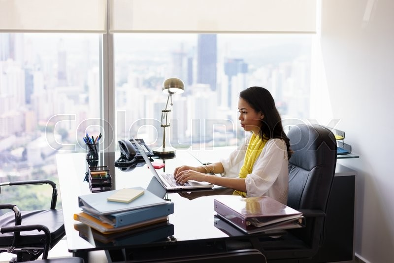 Stock image of 'Adult businesswoman sitting in modern office in skyscraper. The secretary writes on laptop pc with serious expression. Wide shot\'