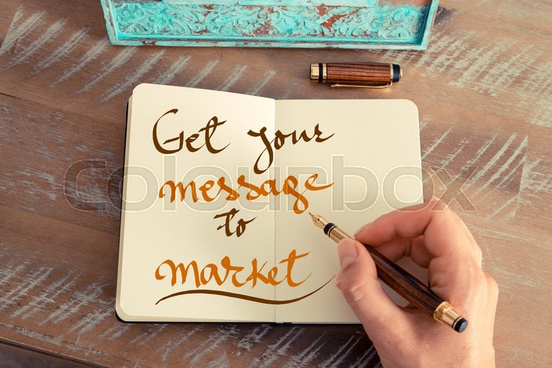 Stock image of 'Retro effect and toned image of a woman hand writing a note with a fountain pen on a notebook. Handwritten text GET YOUR MESSAGE TO MARKET, business success concept'