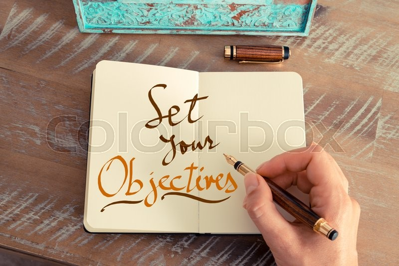 Stock image of 'Retro effect and toned image of a woman hand writing a note with a fountain pen on a notebook. Handwritten text SET YOUR OBJECTIVES, business success concept'