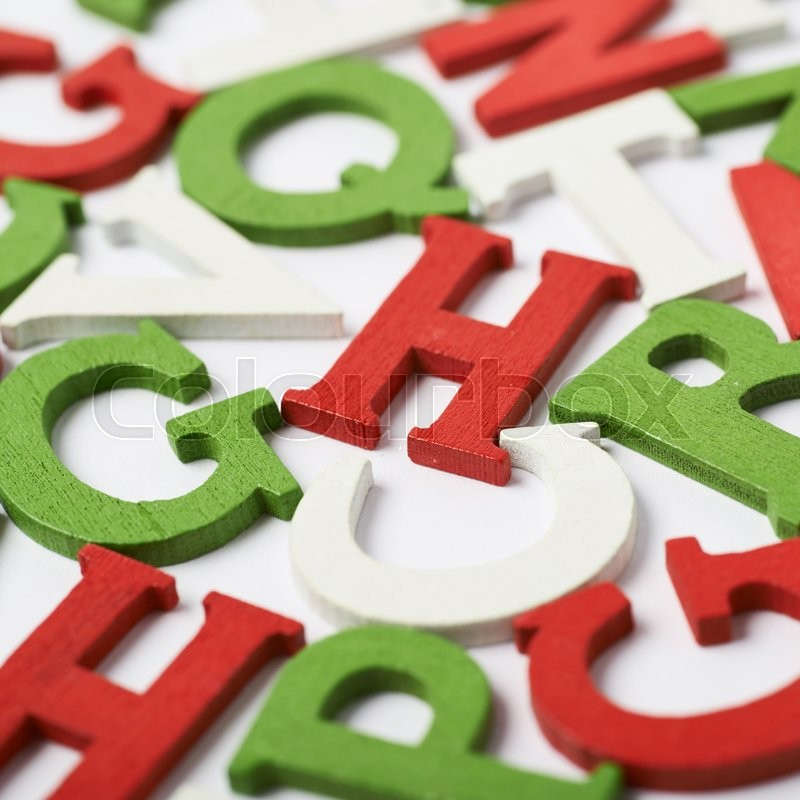 Stock image of 'Surface covered with colorful red, green, white wooden letters as an abstract background composition'