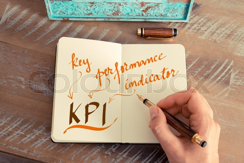 Stock image of 'Retro effect and toned image of a woman hand writing a note with a fountain pen on a notebook. Handwritten text KPI KEY PERFORMANCE INDICATOR, business success concept'