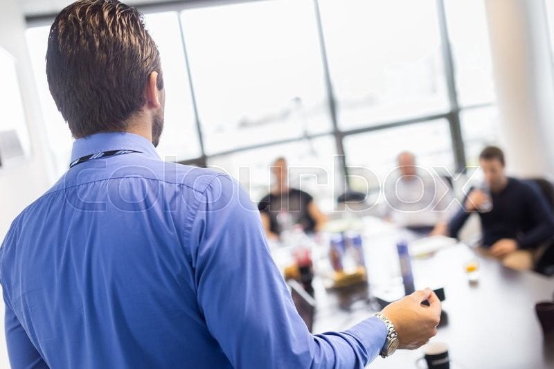 Stock image of 'Business man making a presentation at office. Business executive delivering a presentation to his colleagues during meeting or in-house business training, explaining business plans to his employees. '