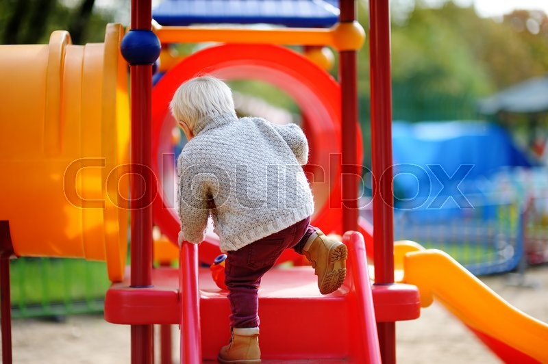 Stock image of 'Beautiful toddler boy having fun on playground'