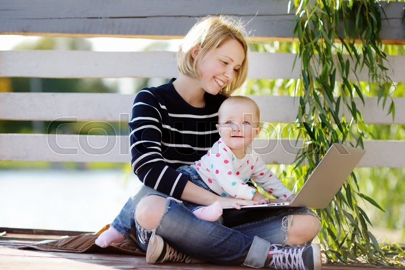 Stock image of 'Young busy mother with her adorable baby girl working or studying on laptop in the park'