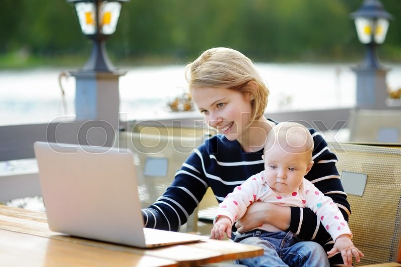Stock image of 'Young mother with her adorable baby girl working or studying on her laptop in outdoor cafe'