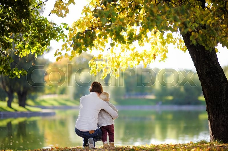Stock image of 'Woman and her adorable toddler son in sunny park'