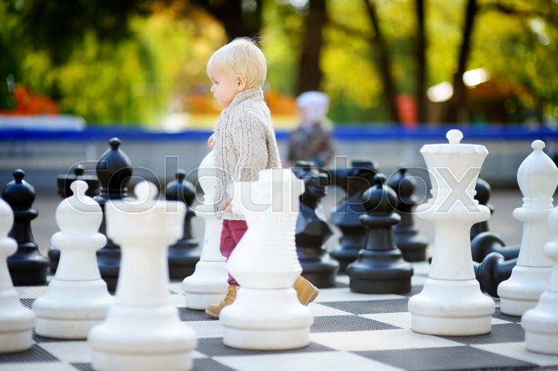 Stock image of 'Toddler boy playing giant chess outdoors'
