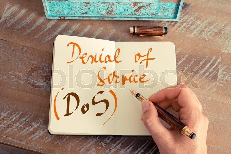 Stock image of 'Retro effect and toned image of a woman hand writing a note with a fountain pen on a notebook. Handwritten text DOS DENIAL OF SERVICE, business success concept'