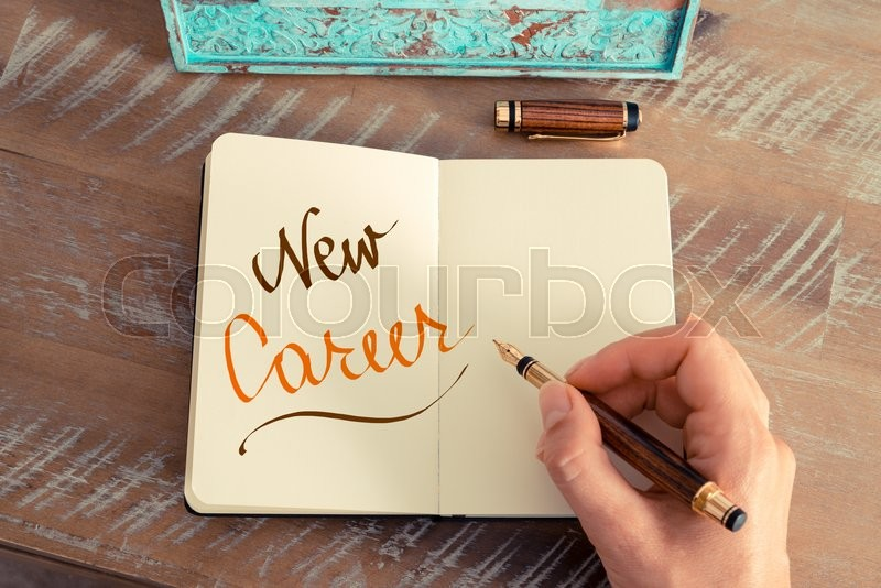 Stock image of 'Retro effect and toned image of a woman hand writing a note with a fountain pen on a notebook. Handwritten text NEW CAREER, motivation concept'