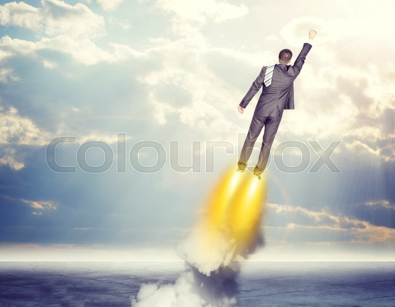 Stock image of 'Businessman in suit flying in sky with clouds, rear view'