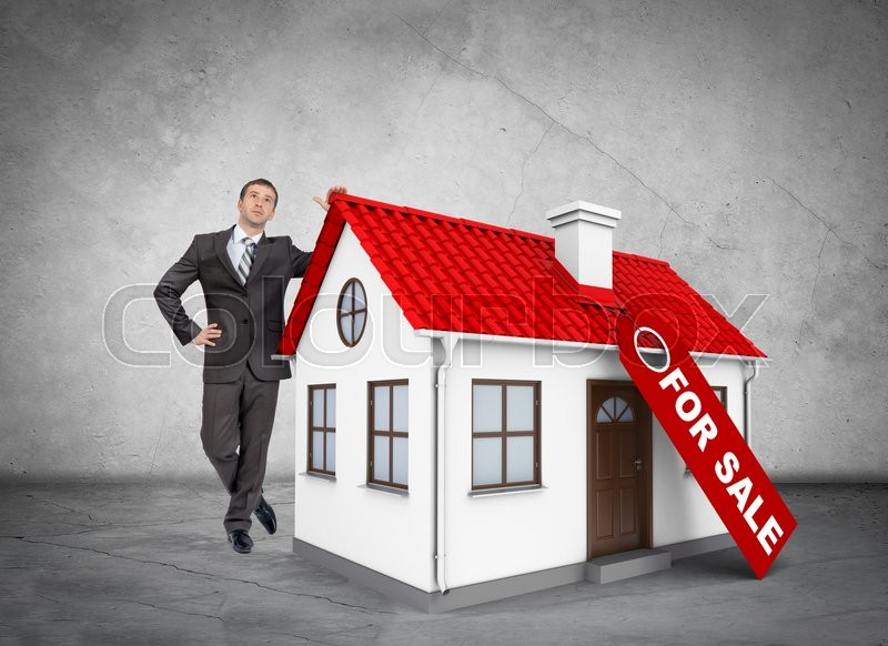 Stock image of 'Businessman with house for sale on grey wall background'
