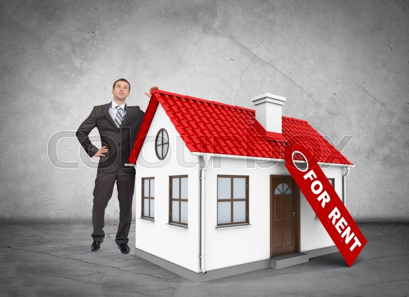 Stock image of 'Businessman with house for rent on grey wall background'