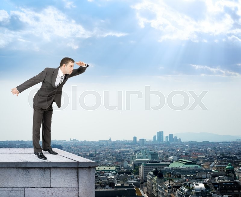 Stock image of 'Businessman looking forward on building roof and cityscape background'