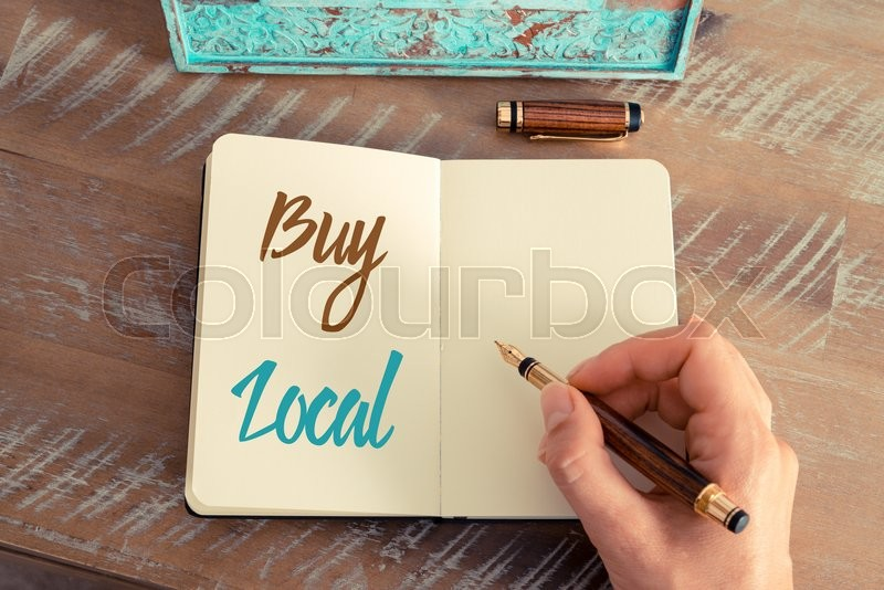 Stock image of 'Retro effect and toned image of a woman hand writing a note with a fountain pen on a notebook. Handwritten text BUY LOCAL, motivation concept'