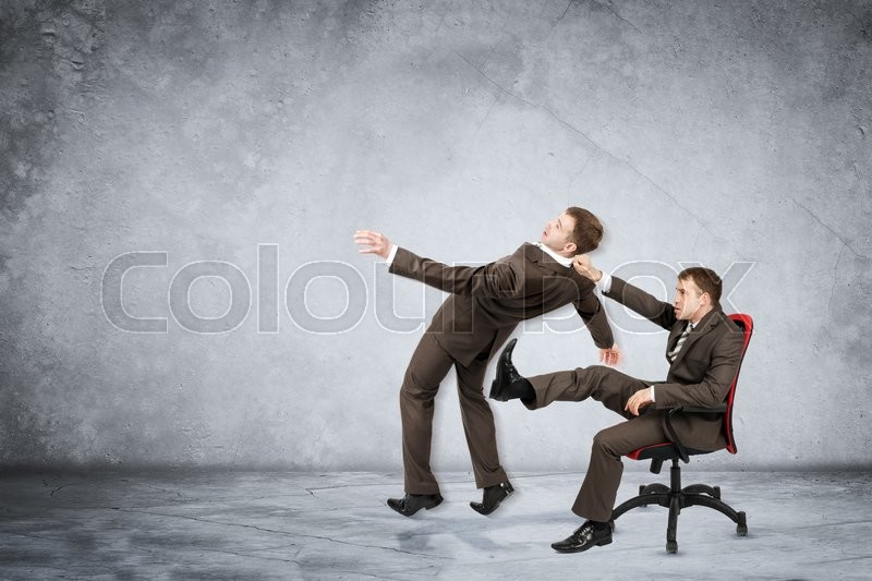 Stock image of 'Businessman sitting on chair and kicking man on grey wall background'