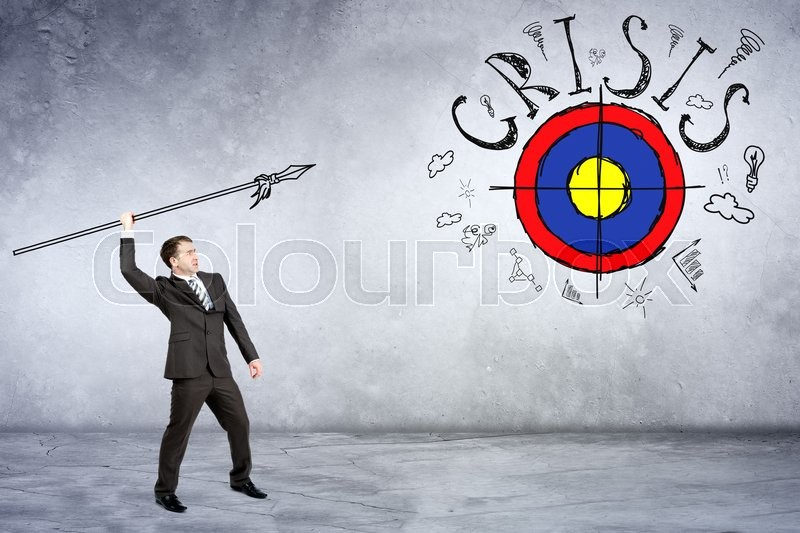 Stock image of 'Businessman throwing spear to darts with word crisis on grey wall background'
