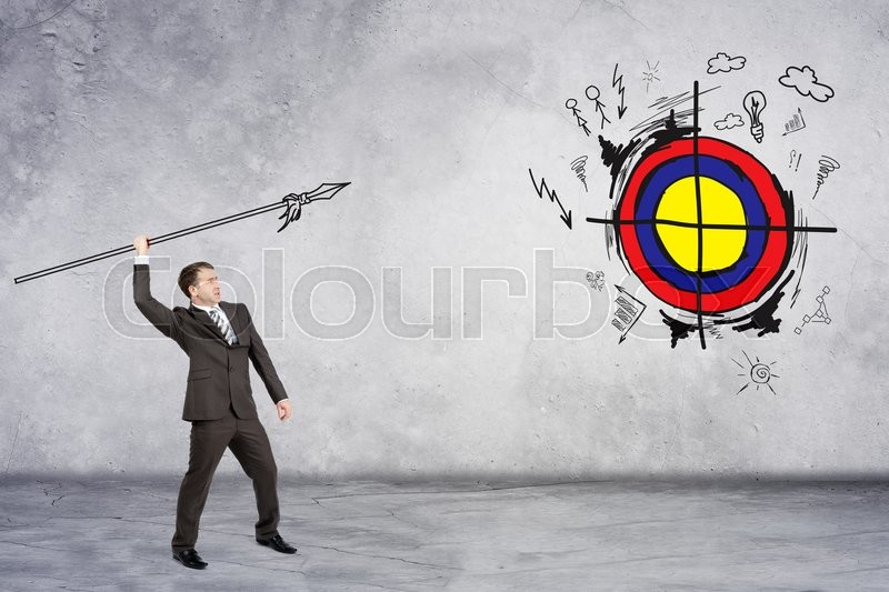 Stock image of 'Businessman throwing spear to darts on grey wall background'