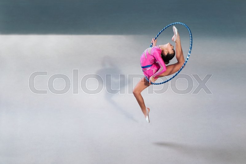 Stock image of 'gymnast in a beautiful pink dress with a hoop in a jump'