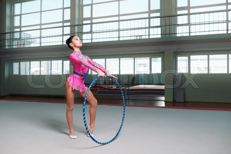Stock image of ' athlete beautiful girl in a pink dress stands proudly with a hoop'