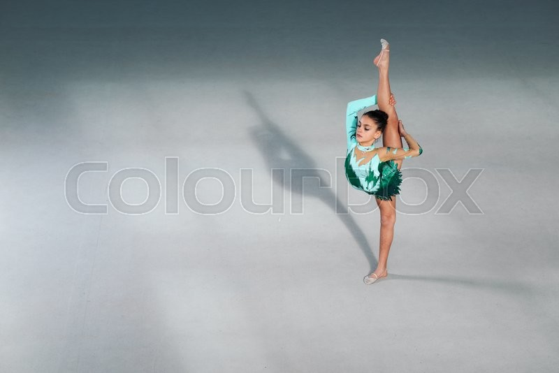 Stock image of 'gymnast performs in a green suit with a balance of splits'