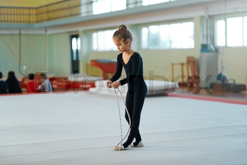 Girl trains with a rope in rhythmic gymnastics, stock photo