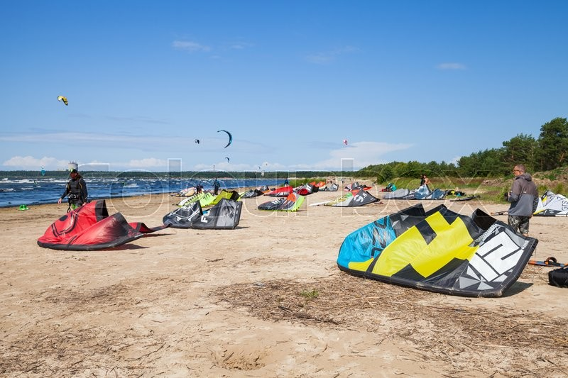 Editorial image of 'Sosnovy Bor, Russia - July 19, 2015: Kitesurfers on the beach prepare sport equipment for riding. Gulf of Finland, Russian coast'