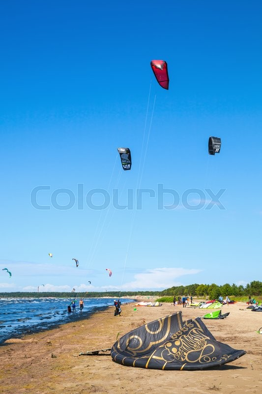 Editorial image of 'Sosnovy Bor, Russia - July 19, 2015: Kitesurfers prepare equipment for riding on the beach. Gulf of Finland near the Leningrad Nuclear Power Plant'