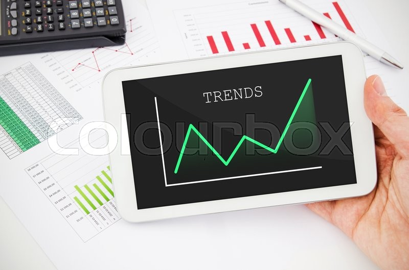 Stock image of 'Businessman working with tablet pc. Report charts in background'