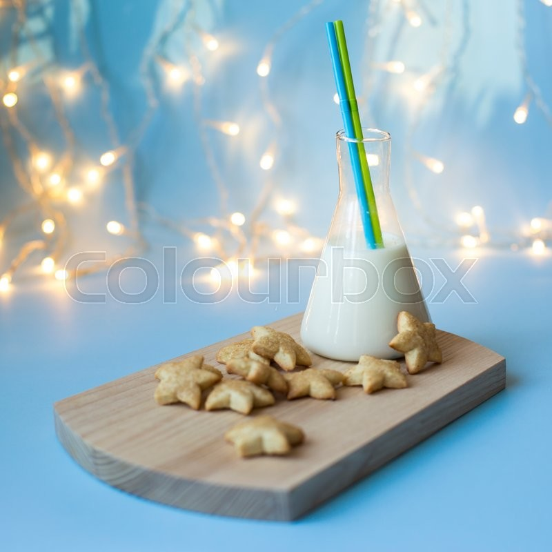 Stock image of 'Plate of cookies and glass of milk near Christmas tree'